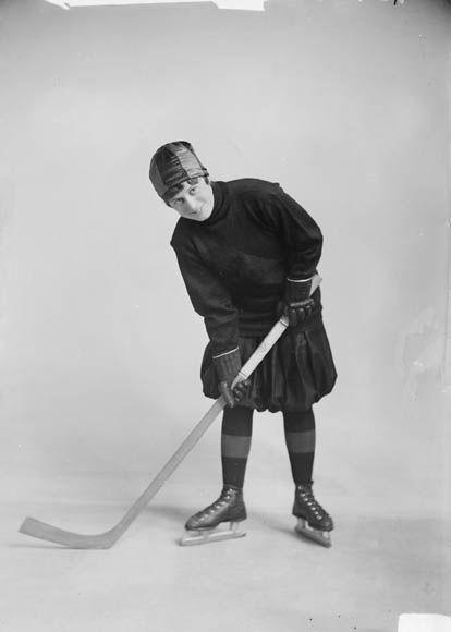 """L'une des premières joueuses professionnelles de hockey: Mlle Eva Ault, 1918.   """"Avec le départ des hommes pour l'Europe durant la Première Guerre mondiale, les femmes ont eu leur première occasion de jouer au hockey professionnel. Eva Ault est devenue une des préférées des amateurs de ce sport. La carrière des premières joueuses de hockey professionnelles s'est toutefois terminée à l'armistice."""" (Site de BAC).  William James Topley/Bibliothèque et Archives Canada/PA-043029"""