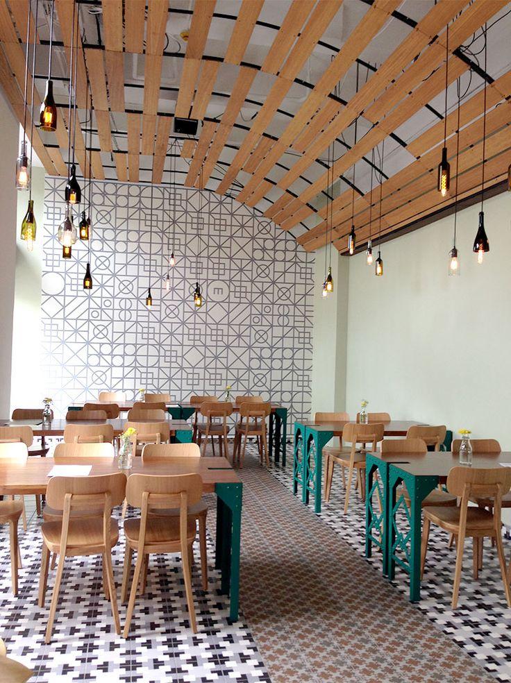 Die gewoelbte Decke aus Holzpanelen von der Flaschenlampen herunterhaengen, machen das Design Cafe im Industrial look erst Recht gemuetlich.