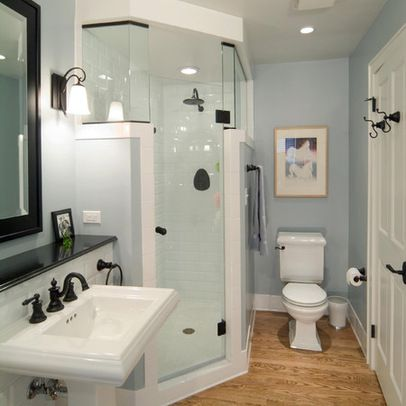 Corner shower with glass door and higher glass sides. Wall on the outside can be used for hook or towel rod