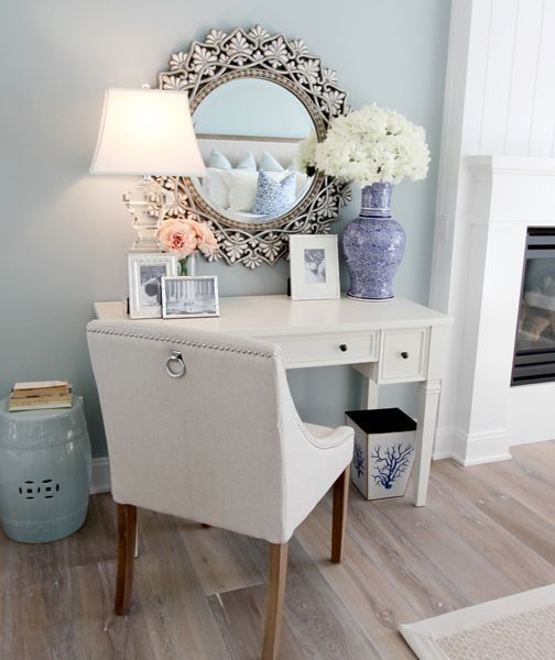 Who wouldn't want to finish up work at home with a place like this? Lamp + mirror + fresh flowers + cushioned chair + pictures + simple desk = such a relaxing work environment!