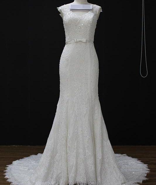 Vestido de noiva sereia todo rendado, cinto com laço, transparência nas costas. Via Brasil Noivas.