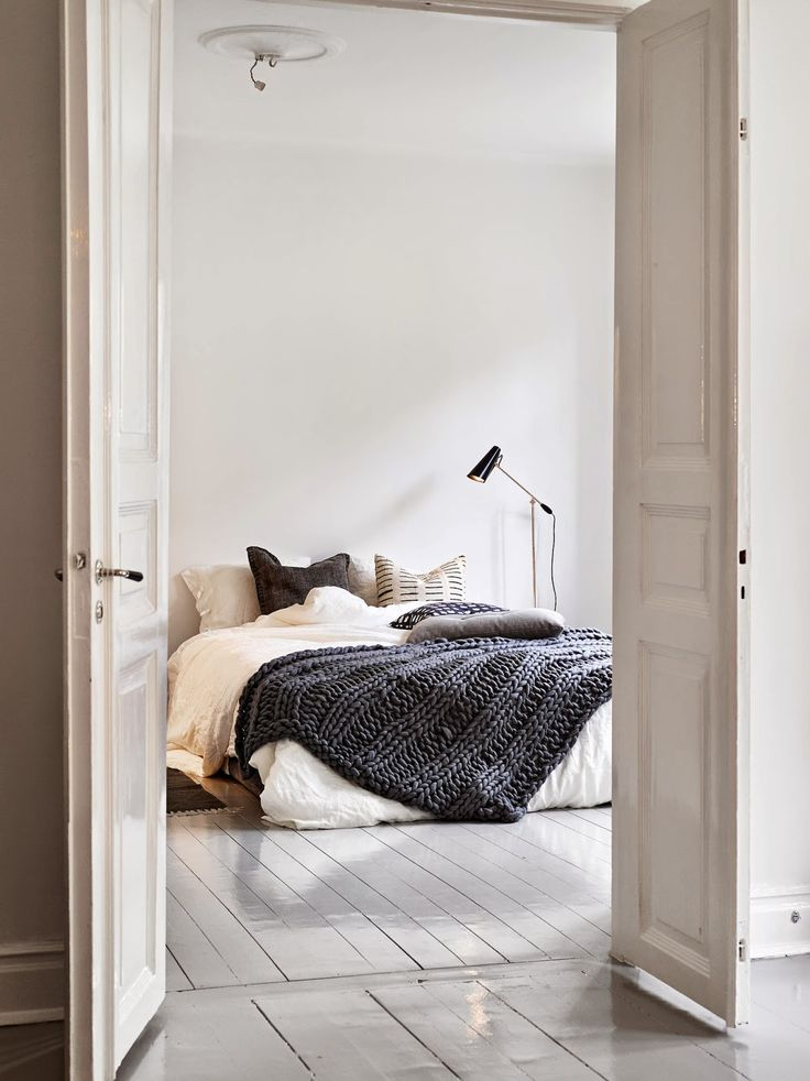 A Swedish apartment with a cosy bed and glossy grey floor Wolldecke selbstgestrickt mega klasse cool haben will