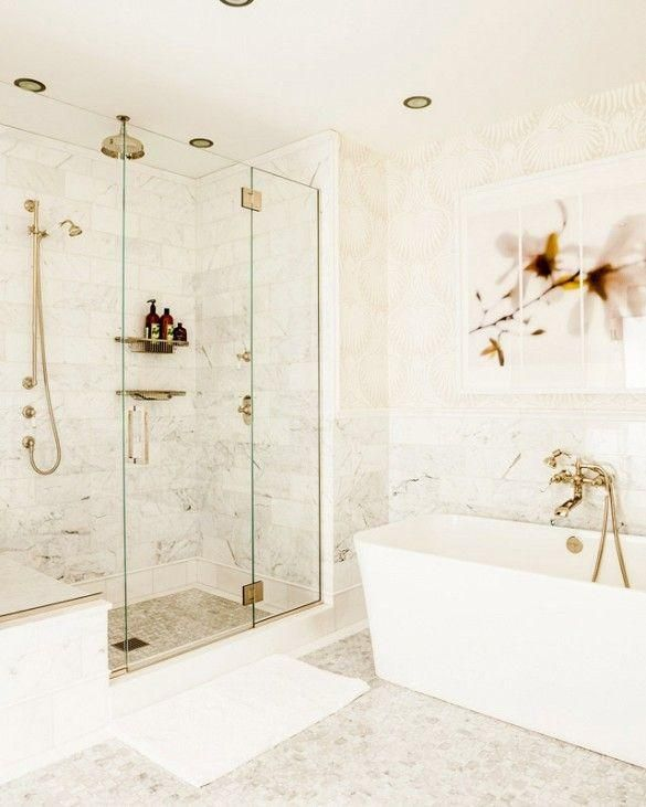 White bathroom with oversized flower art photography, a modern free-standing bathtub with brass hose faucet and a gorgeous walk-in shower with brass rain shower head, detachable shower head and built-in shelving, all in brass.