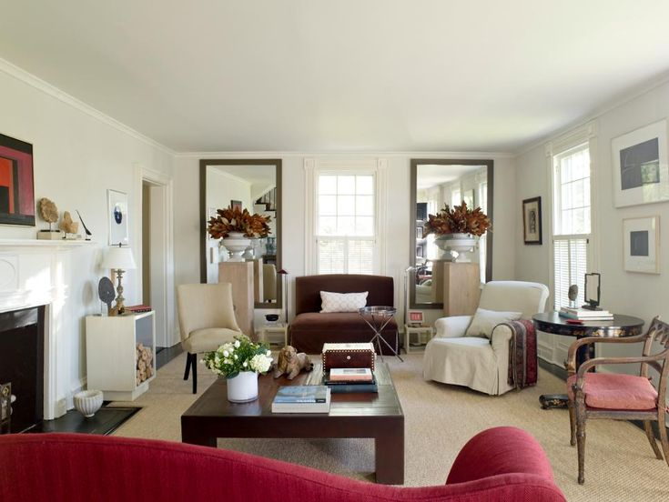 In a living room with a white backdrop, chocolate brown furnishings and red accessories can make a strong statement. Designer Matthew Patrick Smyth pairs red and brown together as complementary shades. The warm tones in each color can be used to create a cozy living room environment.