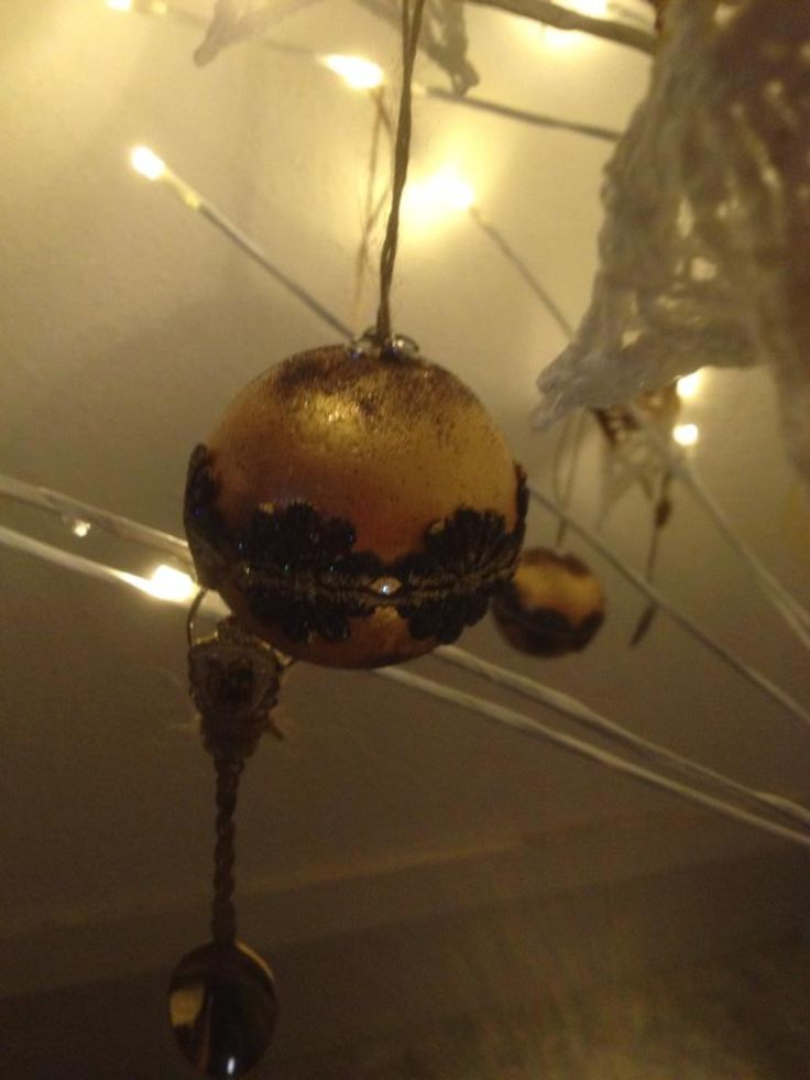 Styrofoam bauble, paint it gold, then partially bronze it, add a layer of lace detail around the middle with pva glue, add a jute string loop to the top, secure with pva glue, add some glitter paint to the lace..walahhhhh!