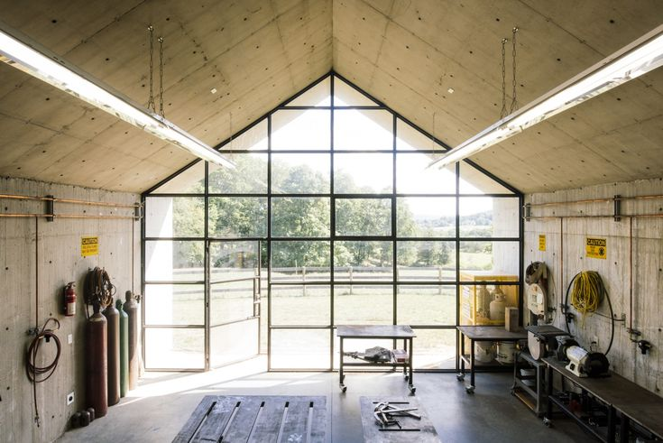 At one end of the studio is a gabled wall of gridded steel windows with embedded lights and an operable door.The studio is lighted by two long rows of off-the-shelf fluorescent hanging lights.