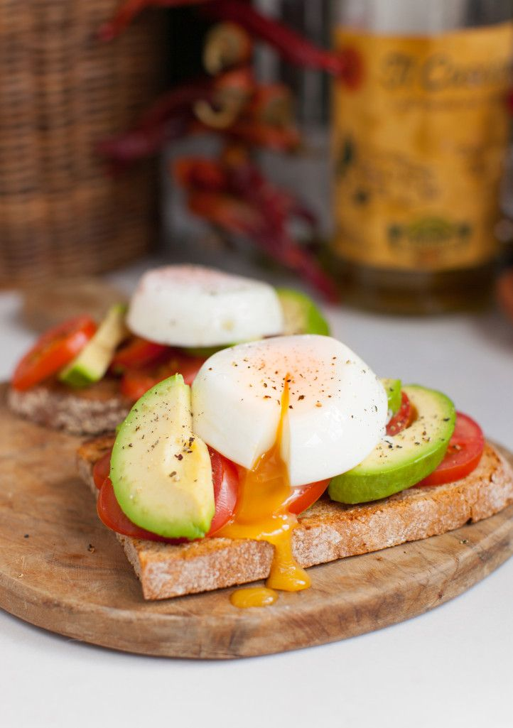 Poached eggs on rye toast with sliced tomatoes and avocado