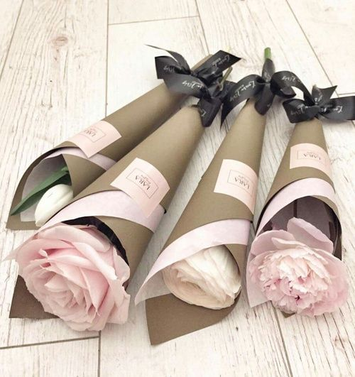 Wrapping individual flowers in combo tissue and craft paper then tying on the bottom.