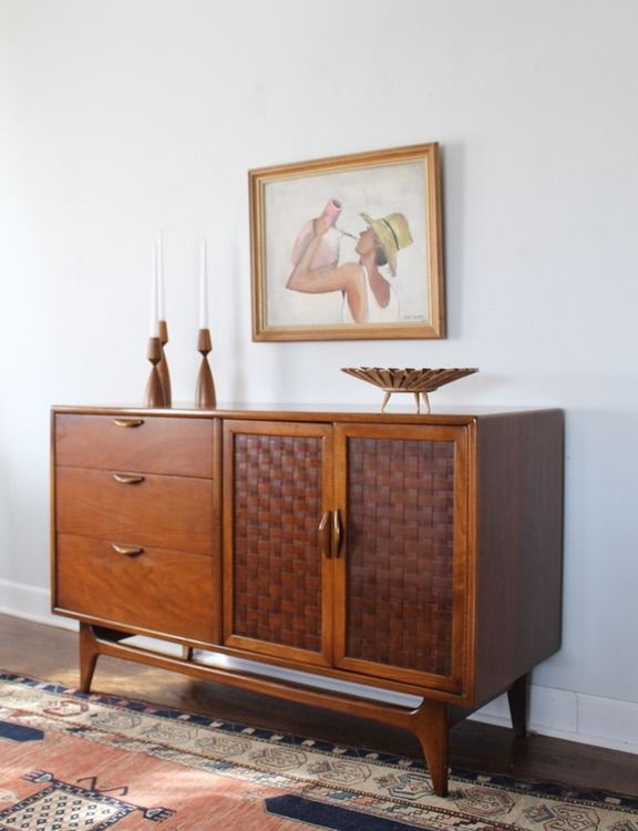 A beautiful buffet made of walnut and oak, featuring three large dovetailed drawers with sculpted wooden pulls.