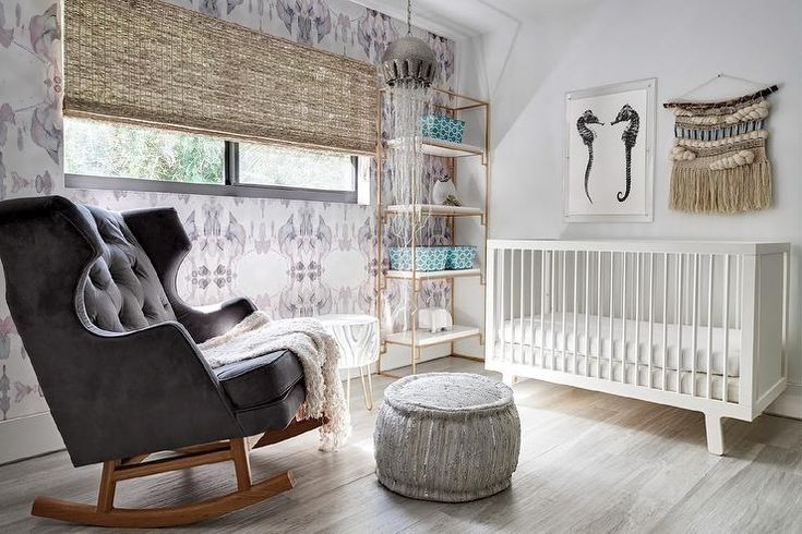 Eclectic contemporary nursery boasts a Babyletto Hudson Crib sits on gray wash wood floors beneath seahorse art and beside a Worlds Away Shadow Gold Leaf & White Lacquer Etagere positioned against an accent wall clad in Eskayel Madagascar Wallpaper framing a window dressed in a bamboo roman shade illuminated by a Currey & Co Medusa Nickel Pendant.