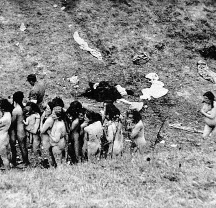 Naked Jewish women some holding their youngsters are from a Ukraine ghetto waiting in line to be executed by Nazis and anti-Semitic Nazi supporters.