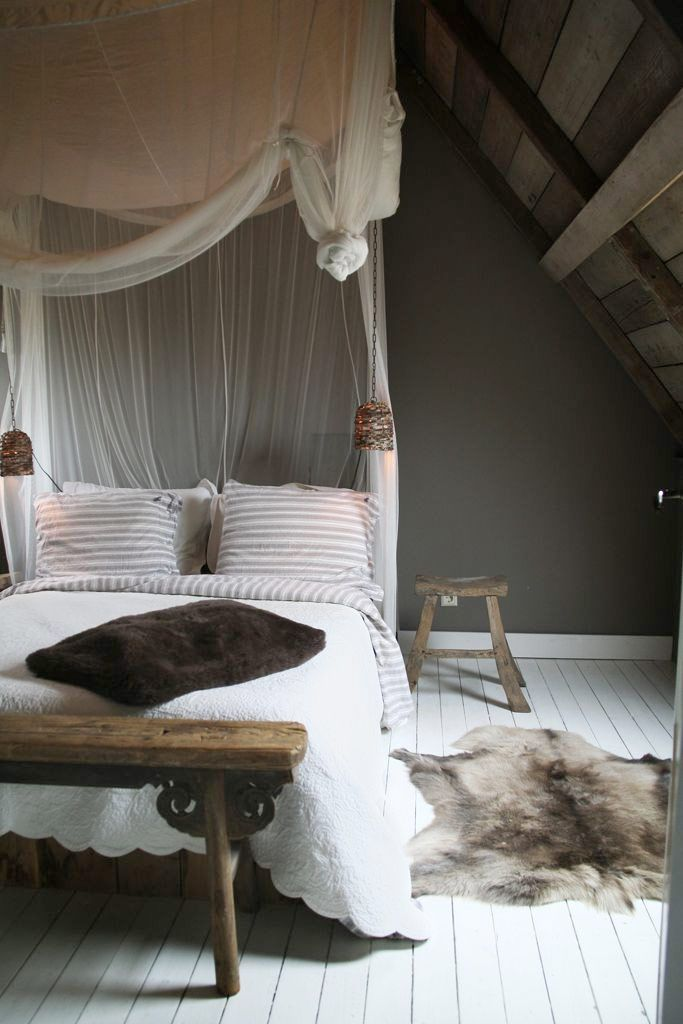 Dreamy escape bedroom with hanging mesh, rustic wooden bench, exposed wooden beams, white bedding