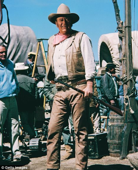 John Wayne on the set of the film, The Undefeated, with covered wagons in the background in 1969.
