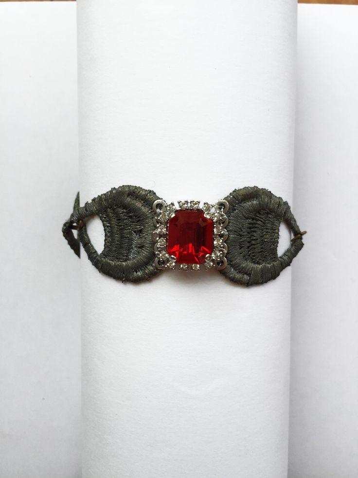 Sencillo brazalete hecho a mano en encaje teñido en plata vieja contrastado con cristal checo de color rojo, aportándole frescura y originalidad. Pieza para lucir en cualquier ocasión.