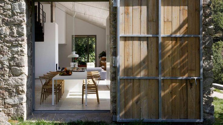Vista exterior de cocina-comedor de casa de campo construida con piedra autóctona por ÁBATON Arquitectura