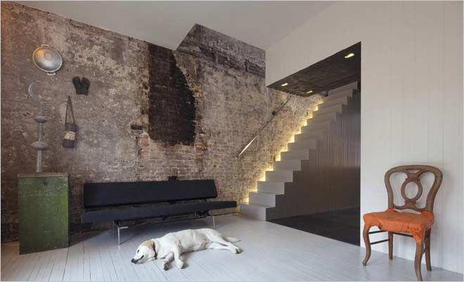 Indirecte verlichting aan trap in modern interieur met oude bakstenen van bestaande stenen muur