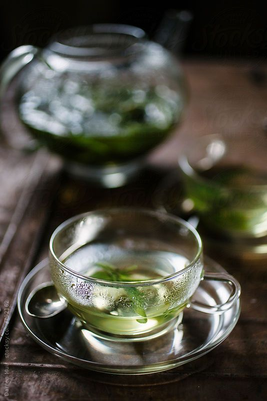 A cup of sage tea on a table,with teapot in the background. by Darren Muir