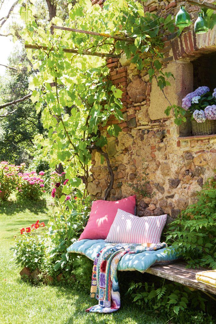 Un banco de madera apoyado en pared de masía. Con colchonetas y plaids de colores 00436205