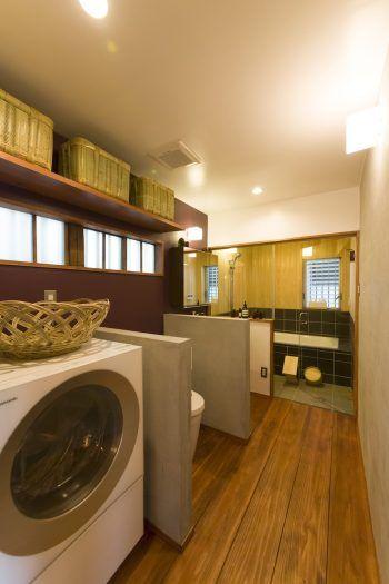 浴室、洗面、トイレ、洗濯機をひとつの空間に。ガラス張りの浴室は、ヒノキの壁と黒のタイルでシックに。