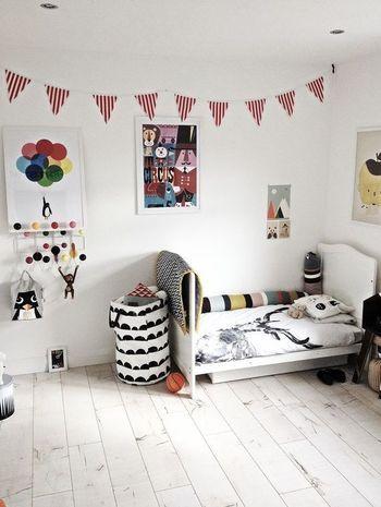 モダンな北欧ファブリックがあふれる子ども部屋。ストライプ柄のガーランドがポップなアクセントに。