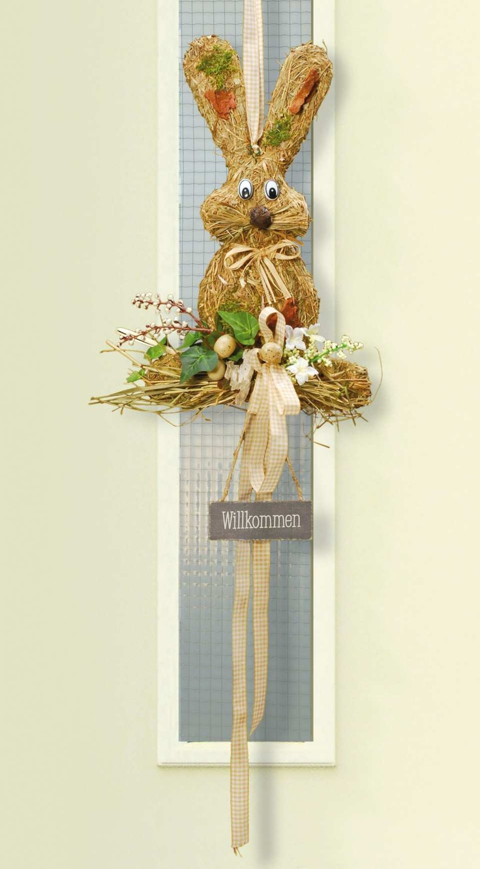 Türdeko Hase - Dieser hübsch dekorierte Hase aus Heu setzt einen schönen Akzent an Ihrer Haustüre. Aufwändig verziert mit Willkommensschild, Eiern, Blüten, Rinden und dem passenden Schleifenband.