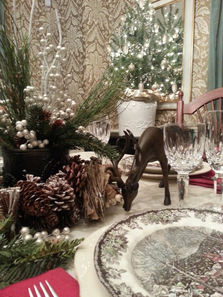 Christmas tablescape with evergreens, pinecones, deer, and Johnson Bros 'Friendly Village' dishes...