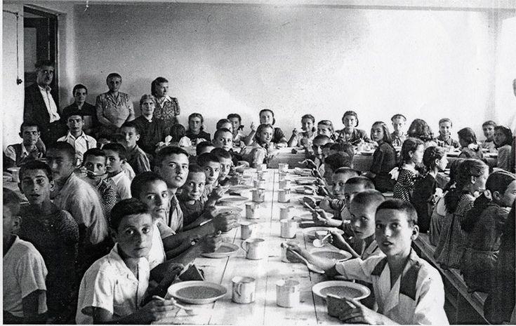 Αυτή η φωτογραφία πρέπει να βγήκε το 1946. Συσσίτιο για τα παιδιά μια εποχή που ένα πιάτο φακές ήταν μέγα ζητούμενο. Διακρίνονται η (θρυλική) διευθύντρια Ευθαλία Χριστοδουλίδου και ο δάσκαλος Άγγελος Άμποτ με τις τραπεζοκόμες. Τα αγόρια κούρεμα «γουλί» για την αποφυγή ψειρών, τα κορίτσια κοτσιδάκια. Τρώνε στο ημιυπόγειο του σχολείου - σήμερα αίθουσα Μουσικής. Το βλέμμα των αγοριών τα λέει όλα… (Αρχείο Δ. Κεραμιδά)