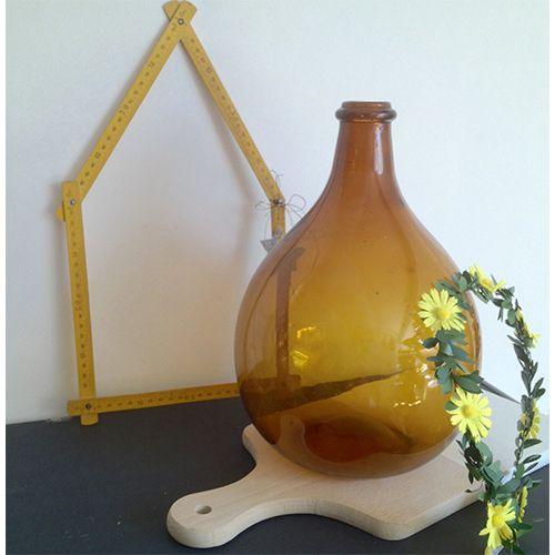 Brocante / Décoration : Dame Jeanne ambrée, aussi appelée Tourie ou Bonbonne, est une grosse bouteille en verre, déshabillée de sa protection en paille.
