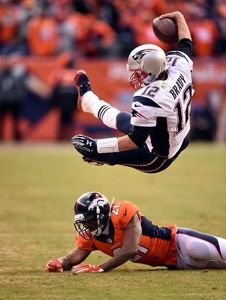 Quarterback Tom Brady (12) of the New England Patriots runs for a first down and is taken down by cornerback Aqib Talib (21) of the Denver Broncos during the AFC championship game at Sports Authority Field at Mile High in Denver, CO on January 24, 2016.