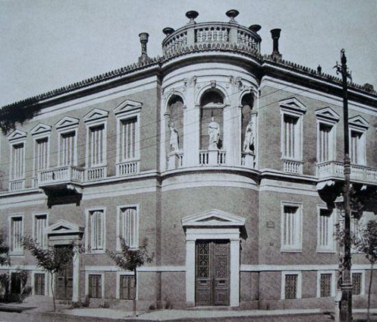 Το εντυπωσιακό κτίριο που βρισκόταν στην οδό Φιλελλήνων και Σιμωνίδου. Στα δεξιά του υπήρχε η Αγγλικανική εκκλησία του Αγ. Παύλου. Νεοκλασικά κτίσματα οικοδομήθηκαν στο κέντρο της πόλης με την υπογραφή Ελλήνων και ξένων αρχιτεκτόνων, οι οποίοι ενέταξαν αρχιτεκτονικά ευρήματα της αρχαίας Ελλάδας. Πέραν από τους κίονες των αρχαίων ναών, πηγή έμπνευσης αποτέλεσαν δύο σημαντικά έργα: το κυλινδρικό μνημείο του Λυσικράτη και ο οκταγωνικός πύργος των Αέρηδων στην Πλάκα. Φωτογράφος Γεώργιος…