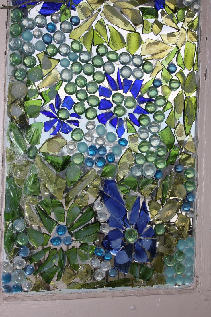 close up of mosiac window using colored broken glass and adhered using a silicone base clear gel.  This particular adhesive is waterproof, so can hang it outside in garden.