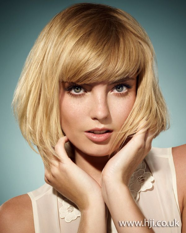 A layered blonde bob was prepped with mousse and blow-dried using a round brush to create a smooth finish with enhanced layers.