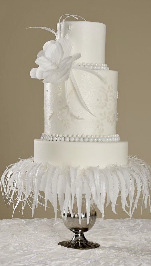 All white wedding cake. Would create this using wafer paper for the feather and a sp flower and fondant pearls