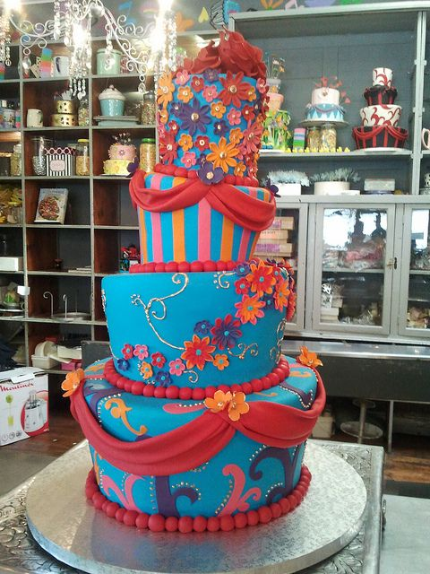 4-tier Mad Hatter wedding cake covered in turquoise fondant decorated with moulin rouge twirls, drapes, op art & multi daisies, piped twirls, & stripes in red, pink, purple, orange & gold by Charly's Bakery, via Flickr