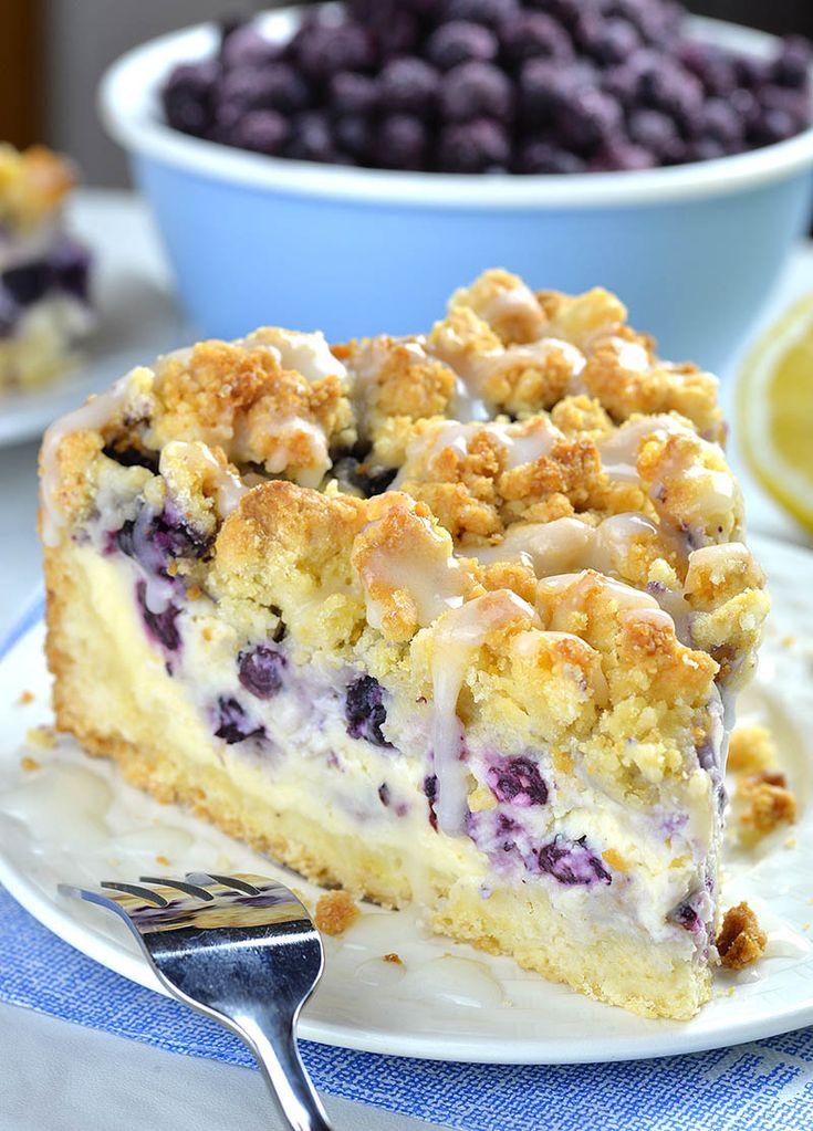 Stück Blaubeerkäsekuchen-Streuselkuchen auf weissem Teller vor Schüssel voll …  – Crumb cake