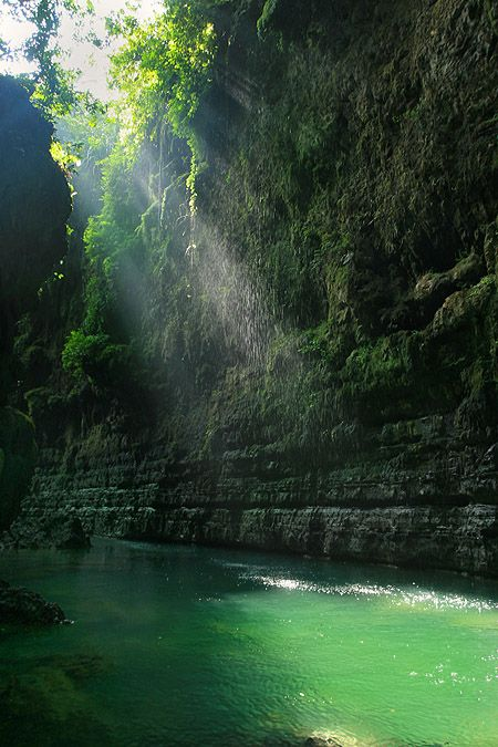 """ Green Canyon "" in Pangandaran , Ciamis - West Java , Indonesia.  The ray of lights came from two cliffs with the green surroundings and its green water."