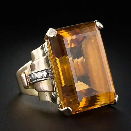 This super-size bauble, circa 1950, presents a 40-plus carat emerald cut citrine with a shimmering butterscotch, orange-gold color. The citrine sits proudly atop a multi-tiered stylized scroll pattern in tri-color gold (yellow, rose and white) which wends its way down the shoulders to the ring shank. A bold gold eye-popper and smile maker!