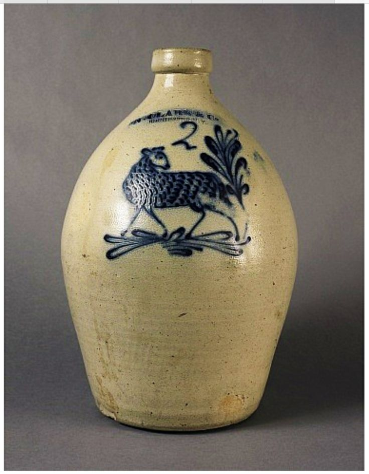 """Keno Auctions 1/18/11 Lot 28:  Description: A Salt-Glazed Cobalt-Blue Decorated Two-Gallon Stoneware Jug with Lamb impressed """"N. CLARK & CO / ROCHESTER N.Y."""" 1841-1852. 15 3/4"""" h During these years George Williams and John Burger ran the Pottery under Clark's name. (Ref: John O'Brien). Condition Report: There are two chips to junction at the handle of spout and a large chip at bottom left of base."""