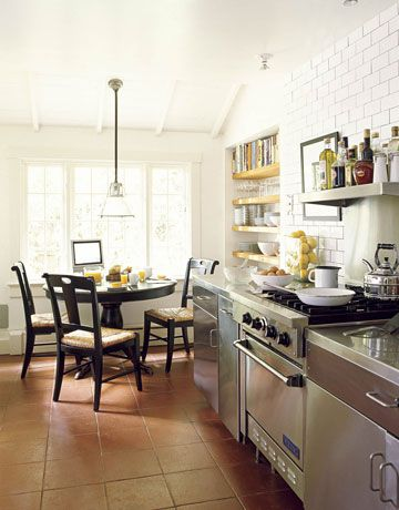 """The """"anti-kitchen,"""" as Mitchell calls it, has been kept as uncluttered and functional as possible. An industrial-style light from Ann-Morris Antiques hangs over a vintage table, where the owner has put a Sharp TV. A niche holds cookbooks and everyday glasses and china conveniently at hand. Stainless-steel cabinets frame the stove, a vintage Viking."""
