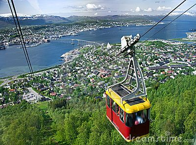 A cable car going up with Tromso panorama in the background.