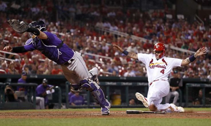 Grichuk, Leake lead Cardinals to an 8-2 win over Rockies  -  July 24, 2017:     Colorado Rockies catcher Tony Wolters, left, dives for the throw from Rockies' Mark Reynolds as St. Louis Cardinals' Yadier Molina, right, scores during the eighth inning of a baseball game Monday, July 24, 2017, in St. Louis. Reynolds was charged with a throwing error on the play Photo: Jeff Roberson, AP / Copyright 2017 The Associated Press. All rights reserved.