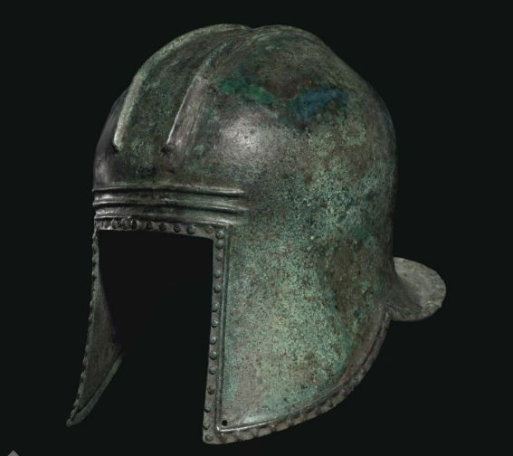 Illyrian helmet, 6th - 5th century BC. Hammered from a single heavy sheet, of domed form, with a wide flaring neck-guard and two raised parallel ridges running front to back across the crown, the raised ridge around the perimeter with circular rivets along the edge, each cheek-guard perforated at the forward tip, with two horizontal ridges across the brow  24.8 cm high Private collection, from Christie's auction