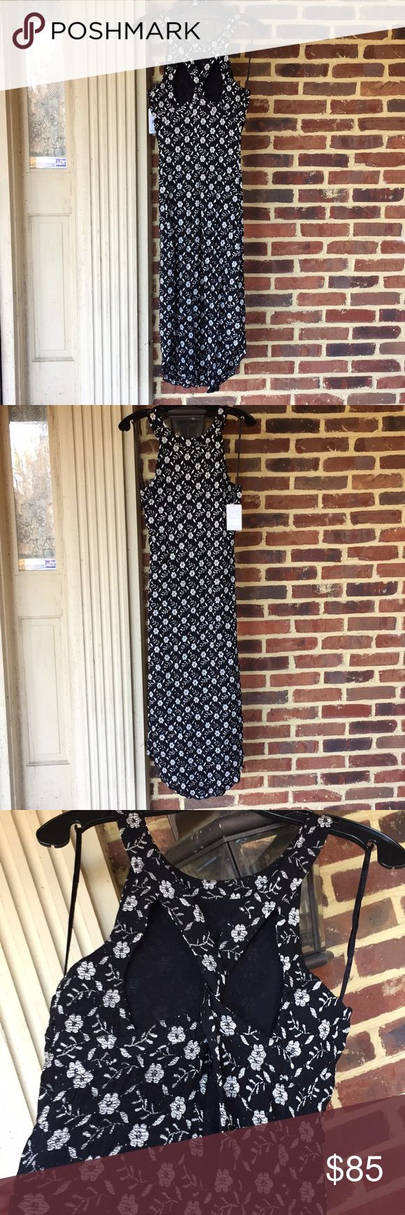 Free People black/silver dress w/ cut-outs- NWT Stunning black and silver maxi dress from Free People. Slightly longer in the center with raised sides at the dress bottom. Pretty and fresh flower pattern and a gorgeous braided cut out design at the back of the dress. Beautiful on. New with Tags. Free People Dresses Maxi