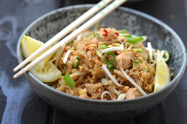 PAD THAI WITH CHICKEN  Ingredients (about 3) 300 grams of chicken 3 eggs approx. 2 cm ginger 2 cloves of garlic 4 spring onions 1-2 tsp chopped chilli 3 tablespoons fish sauce 300 grams of rice noodles  For serving: 1 tray bean sprouts, 1 handful chopped peanuts, a little chopped spring onions, chilli sauce, a few slices of lemon/lime     Chop garlic, chilli, spring onions and ginger Cut chicken into desired sizes Add rice noodles to a bowl and pour boiling water over  (when the water is…