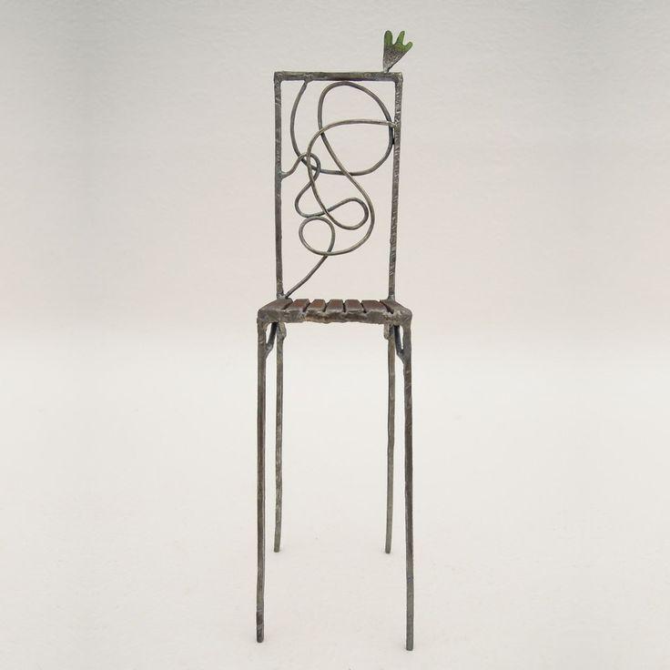 鉄で出来ている椅子のオブジェ。ユニークなハイバックデザイン。卓上サイズながら繊細に作りこまれたディテール。 トップに小さな翼が付いています。正面からの写真。
