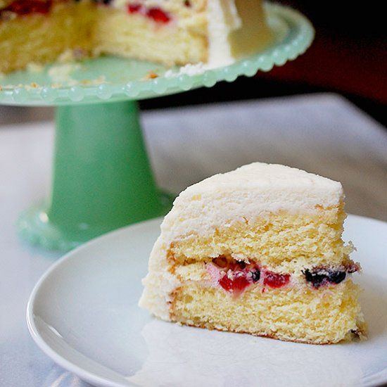 A light and fluffy yellow cake filled with fresh berries and topped with a masca…
