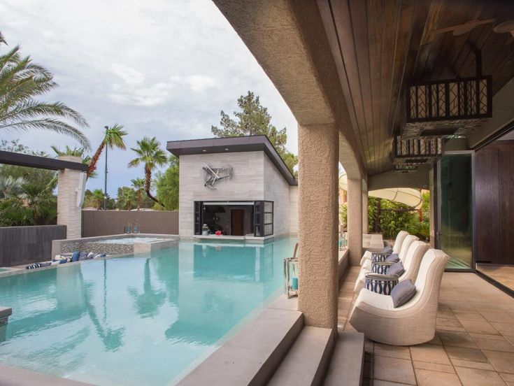 Drew and Jonathan Scott's backyard features this gorgeous swimming pool with an attached pool house. Cozy rocking chairs line the patio outside the pool, providing plenty of seating for guests.