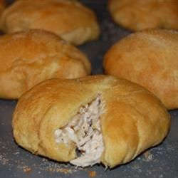 Chicken puffs -  2 skinless, boneless chicken breast halves - cubed  3 tablespoons chopped onion  3 cloves garlic, peeled and minced  3/4 (8 ounce) package cream cheese  6 tablespoons butter  3 (10 ounce) cans refrigerated crescent roll dough