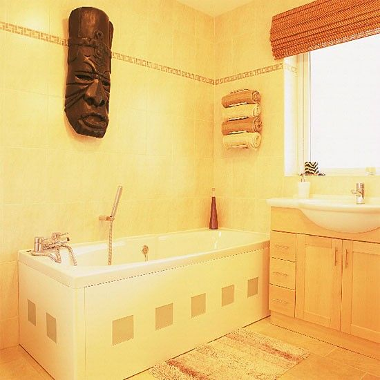 Yellow bathroom with white suite and African mask | housetohome.co.uk