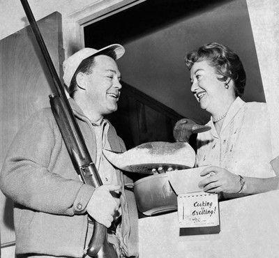Een onsuccesvolle jager geeft zijn vrouw lokaas en een kookboek. Foto: Underwood Archives / Getty Images